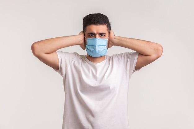 コロナウイルス、伝染病に対する保護。耳を覆い、衛生マスクを着用している男性