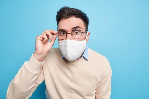 コロナウイルスに対する保護。真面目な青年は、検疫中に公共の場所で使い捨てのフェイスマスクを使用し、セーターを着た眼鏡の縁に手を置きます