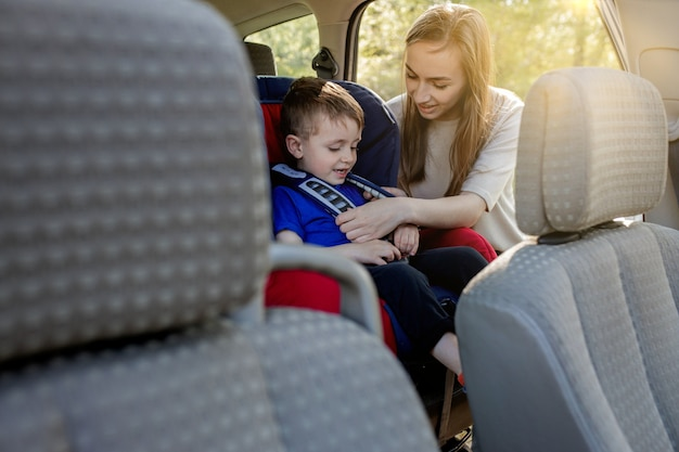 Protection in the car hands of caucasian woman is fastening security belt to child who is sitting