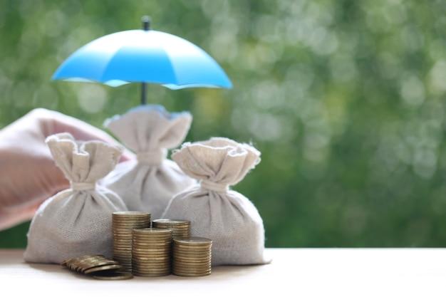 Защита, монеты деньги в сумке с зонтиком на естественном зеленом фоне, финансовое страхование и концепция безопасных инвестиций