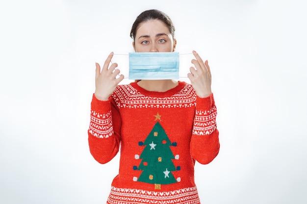 코로나바이러스로부터 보호. 크리스마스 스웨터를 입고 눈에 어리석은 표정을 한 젊은 여성이 의료용 마스크를 얼굴 높이에 들고 있습니다. 흰 바탕.