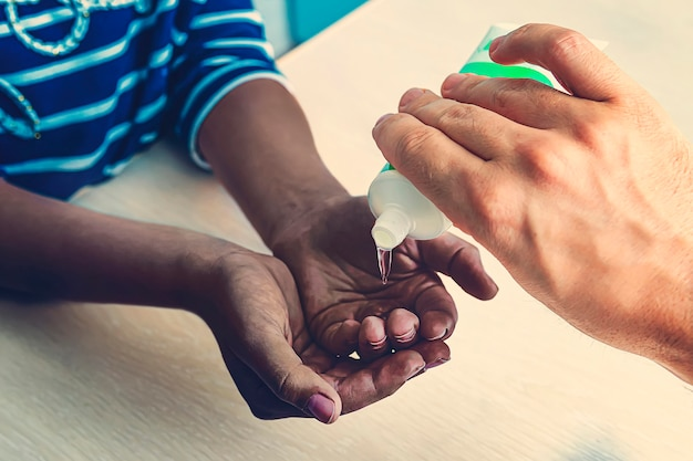 Защита от covid 19. дезинфицирующее средство для рук. европеец наливает дезинфицирующий гель на руки черной девушки дома. забота о людях во время пандемии коронавируса.