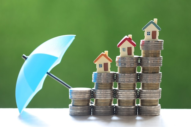 保護、自然の緑の背景に傘を持つコインのお金のスタック上のモデルハウス、金融保険と安全な投資の概念