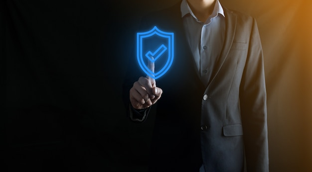 Protection network security computer in the hands of a businessman. business, technology, cyber security and internet concept - businessman pressing shield button on virtual screens. data protection.