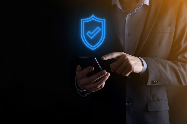 Protection network security computer in the hands of a businessman. business, technology, cyber security and internet concept - businessman pressing shield button on virtual screens data protection.