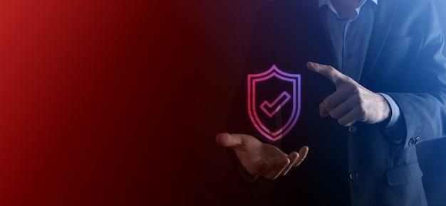 사업가의 손에 있는 보호 네트워크 보안 컴퓨터. 비즈니스, 기술, 사이버 보안 및 인터넷 개념 - 가상 화면의 방패 버튼을 누르는 사업가 데이터 보호