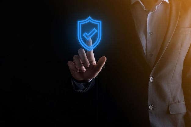 ビジネスマンの手に保護ネットワークセキュリティコンピュータ。ビジネス、テクノロジー、サイバーセキュリティ、インターネットの概念-仮想画面のシールドボタンを押すビジネスマンデータ保護。