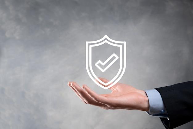 ビジネスマンの手に保護ネットワークセキュリティコンピュータ。ビジネス、テクノロジー、サイバーセキュリティ、インターネットの概念-ビジネスマンが仮想画面のシールドボタンを押します。データ保護。
