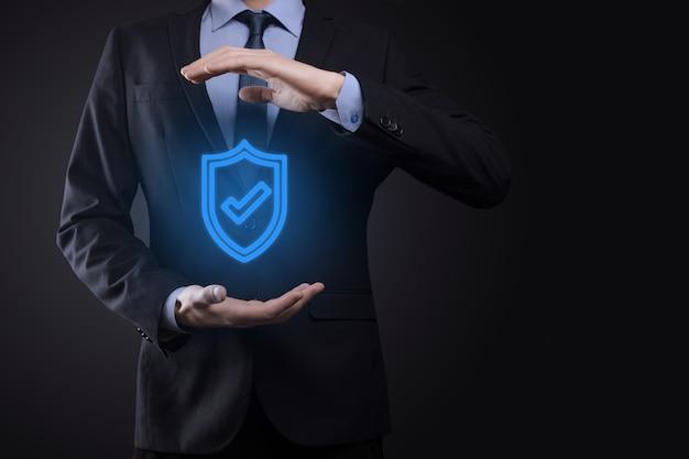 사업가의 손에 보호 네트워크 보안 컴퓨터. 비즈니스, 기술, 사이버 보안 및 인터넷 개념-사업가 가상 화면에서 방패 버튼을 누르면. 데이터 보호.
