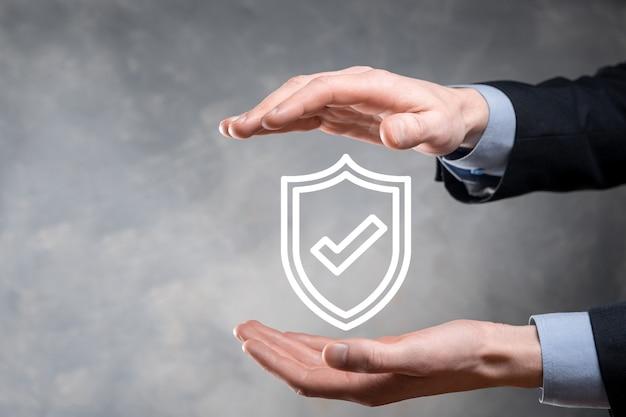 사업가의 손에 보호 네트워크 보안 컴퓨터. 비즈니스, 기술, 사이버 보안 및 인터넷 개념-사업가 가상 화면에서 방패 버튼을 누르면 데이터 보호입니다.