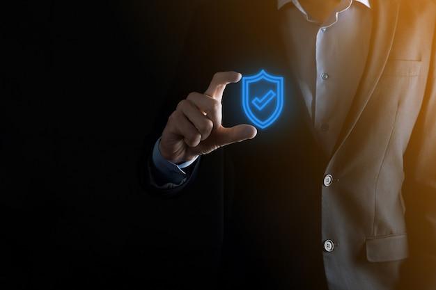 ビジネスマンの手で保護ネットワーク セキュリティ コンピューター。ビジネス、テクノロジー、サイバーセキュリティ、インターネットのコンセプト – 仮想画面でシールドボタンを押すビジネスマン データ保護。