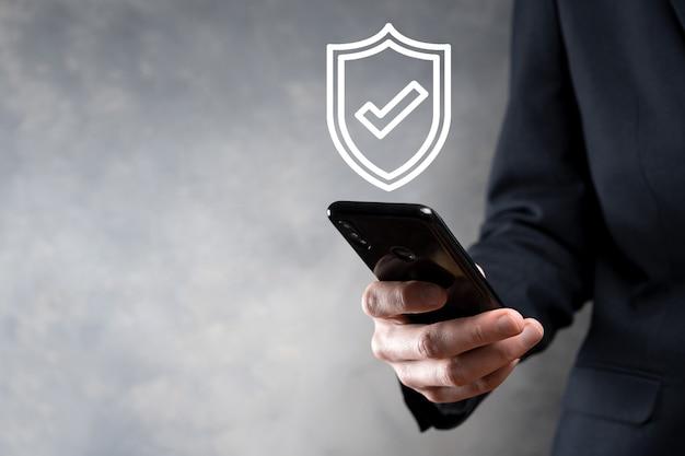 Компьютерная безопасность сети защиты в руках бизнесмена. бизнес, технологии, кибербезопасность и интернет-концепция - бизнесмен, нажав кнопку щита на виртуальных экранах защита данных.