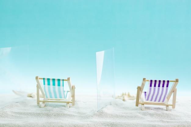 Охрана на пляже. шезлонги разделены стеклянными перегородками на песке. социальное дистанцирование.