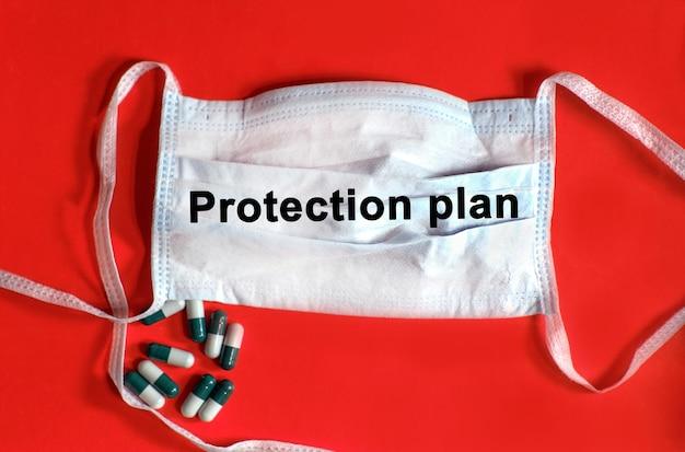 План защиты - текст на защитной маске, таблетки на красном фоне