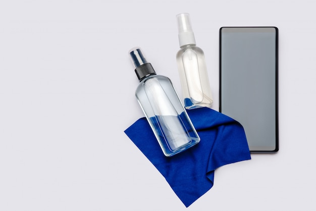 Protection or sanitation against viruses or germs - mobile phone cleaning or disinfection with sanitizer antiseptic spray and cloth