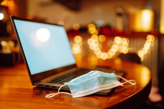 Защитная стерильная медицинская маска на клавиатуре открытого ноутбука.