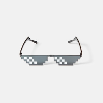 Protective art pixel glasses using for work with computers screens, phones and tv on a light grey wall, copy space.