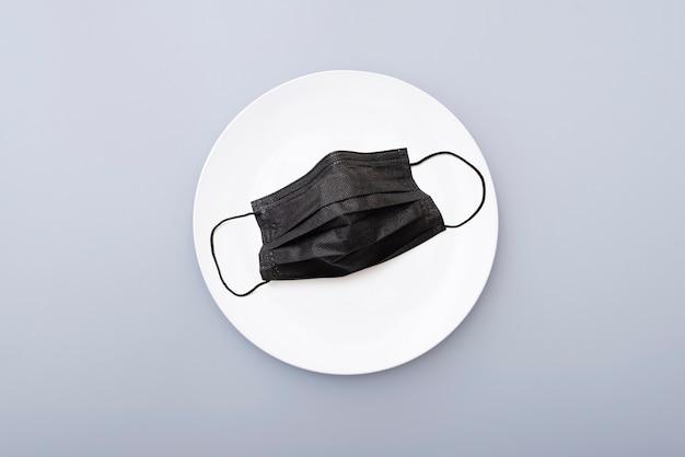 Защитная черная маска на белой керамической пластине, вид сверху. креативная концепция изображения