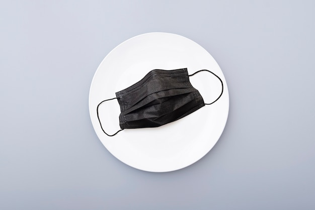 Protective black mask on a white ceramic plate, top view. creative concept picture