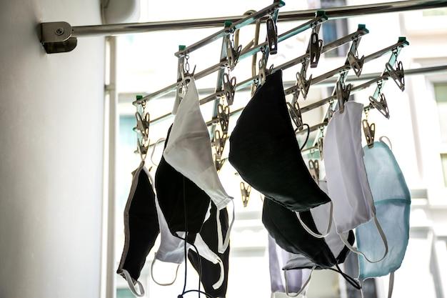 Защитная тканевая маска для лица висит на вешалке для одежды после стирки для сушки и повторного использования.