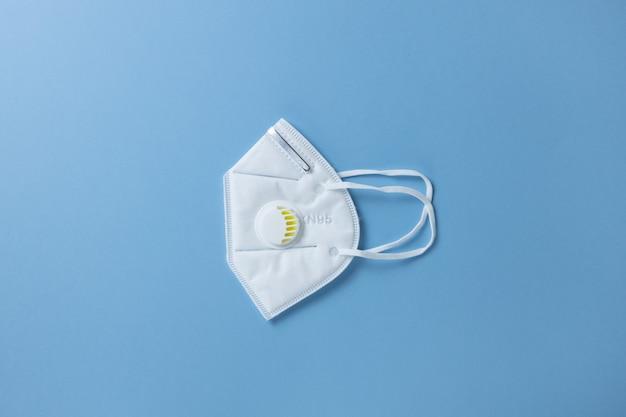 Защитная маска для лица n 95, строительный респиратор с гелевым фильтром на пастельно-голубой стене, крупным планом, ровно, минимал. концепция гигиены, предотвращение распространения вирусных инфекций, забота о здоровье, вред.
