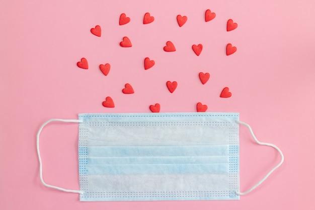 Защитная маска для лица на розовом фоне с красными сердцами. плоская планировка, копия пространства.
