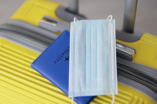 Защитная маска для лица с паспортом, лежащая на желтом чемодане, правила полета крупным планом во время covid
