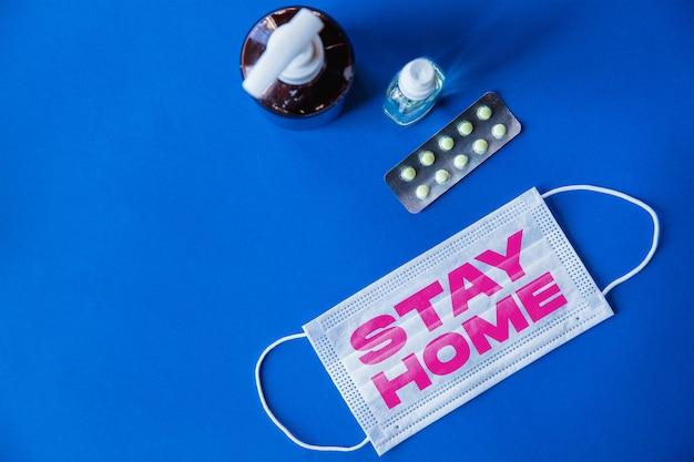 파란색 배경에 stay home이라는 단어가 있는 보호용 안면 마스크, 전염병 확산의 개념, 바이러스 2020, 의학, 의료. 전세계 전염병, 검역 및 격리, 보호. 카피스페이스.