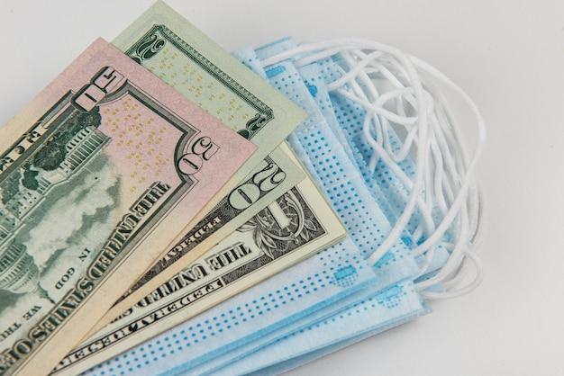 保護マスクと多くの米ドル紙幣