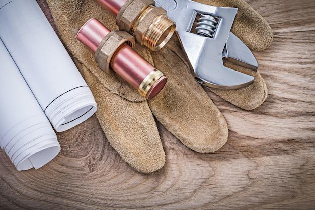 Защитные перчатки медная водопроводная труба чертежи шланг штуцеры разводной ключ на деревянной доске сантехника концепции
