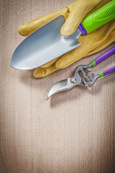 Protective gloves hand spade secateurs on wooden board gardening concept.