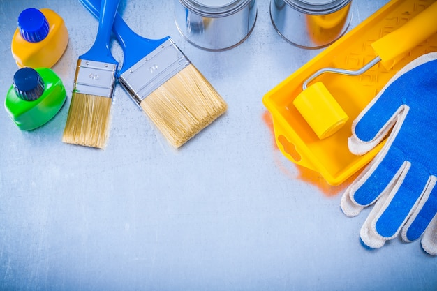 Protective gloves paint brushes roller tray cans and bottles on metallic background construction concept