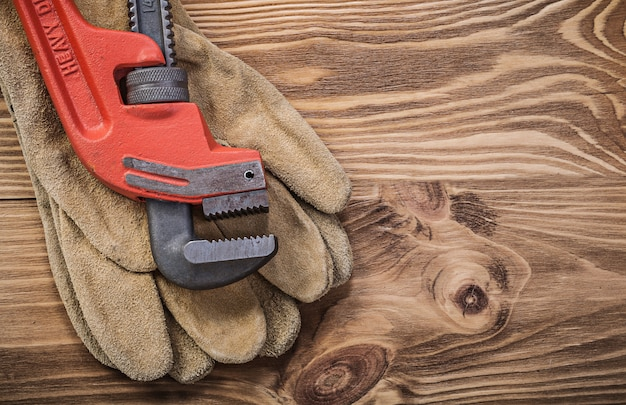 Protective gloves pipe wrench on wooden board construction concept