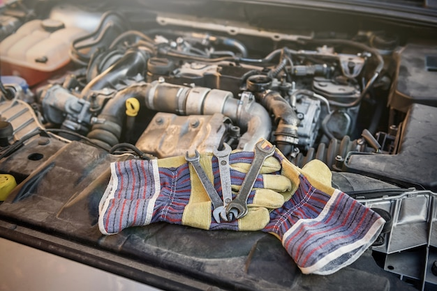 車のエンジンにスパナを付けた保護手袋