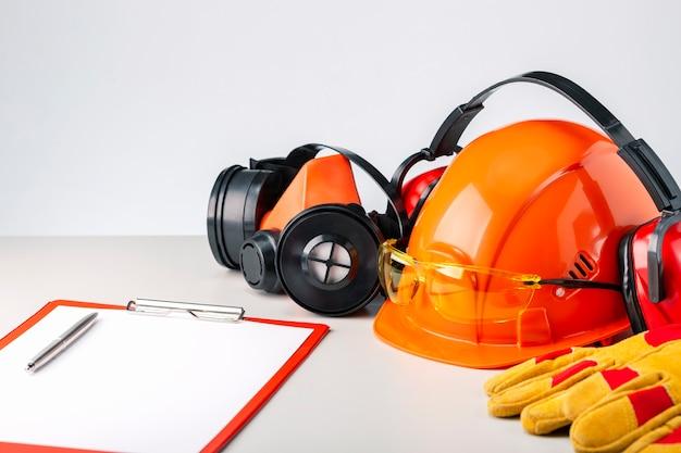 灰色の表面に保護用のヘルメット、ヘッドフォン、手袋、眼鏡、クリップボード。建設の安全性。