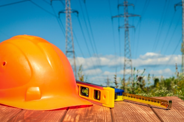 Protective helmet, headphones, gloves on a wooden table, against high voltage posts