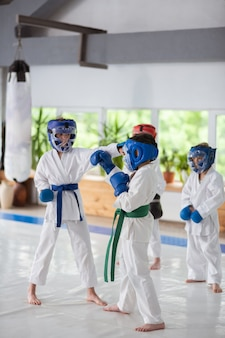 保護用ヘルメット。白い着物と保護用ヘルメットをかぶった子供たちが一緒に練習