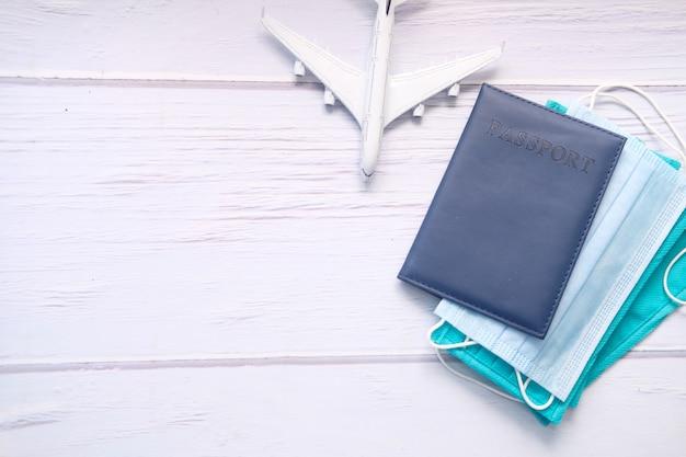 テーブルの上の保護マスク、飛行機と青い色のパスポート。