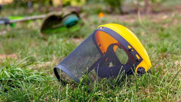 Защитная маска для стрижки травы и триммер в саду на траве