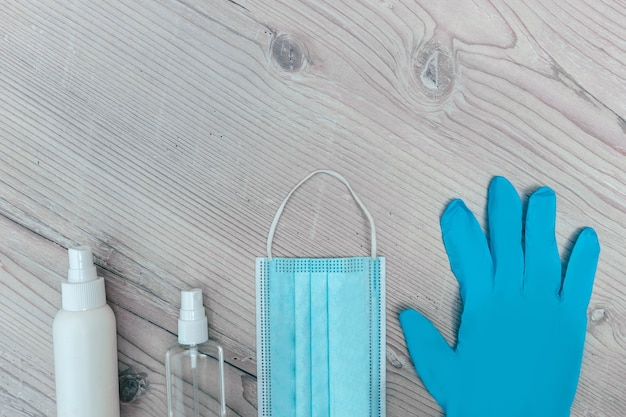 Защитная маска, перчатки и антисептики на деревянном фоне. фото с копировальным пространством