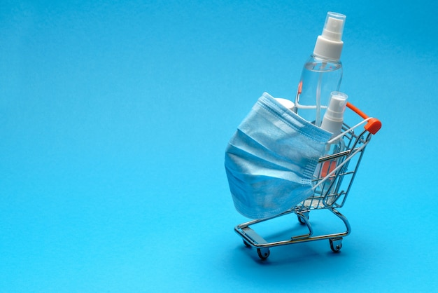 コピースペースのある青い背景の小さなショッピングトロリーカートに保護マスクと抗菌消毒消毒ジェル。