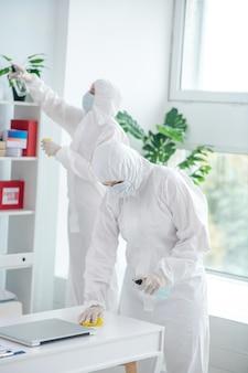 保護対策。防護服と医療マスク消毒テーブルの医療従事者、後ろに立ってクローゼットを掃除している別の労働者