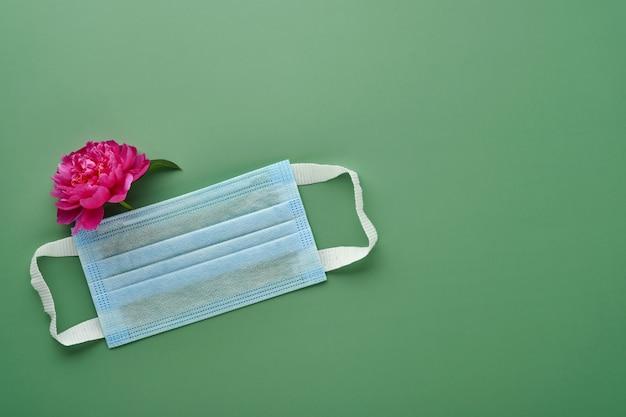녹색 배경에 모란 꽃 보호 의료 얼굴 마스크. 코로나 바이러스 또는 covid-19 대유행 보호의 상징으로 일회용 수술 마스크. 발렌타인 데이, 여성 또는 어머니의 날 개념.