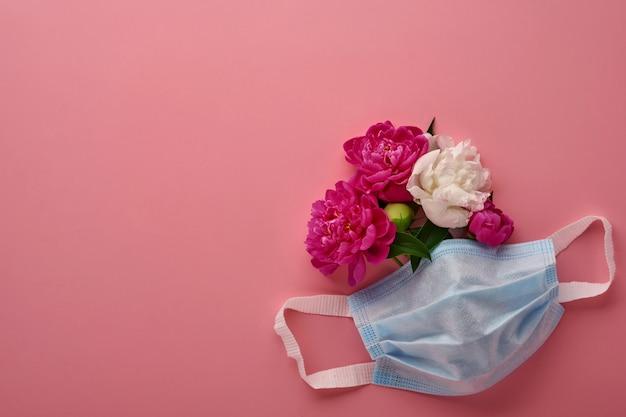 파스텔 핑크 바탕에 모란 꽃과 보호 의료 얼굴 마스크. 코로나 바이러스 또는 covid-19 대유행 보호의 상징으로 일회용 수술 마스크. 발렌타인 데이, 여성 또는 어머니의 날 개념.