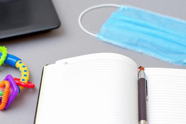 Защитная медицинская маска возле ноутбука и ручки с открытой записной книжкой и погремушкой на сером фоне. выборочный фокус.
