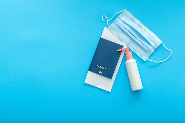 Protective medical mask sanitizer and passport airplane ticket. concept vacation safe travel flights during covid and coronavirus lockdown. flat lay on color blue background with copy space.