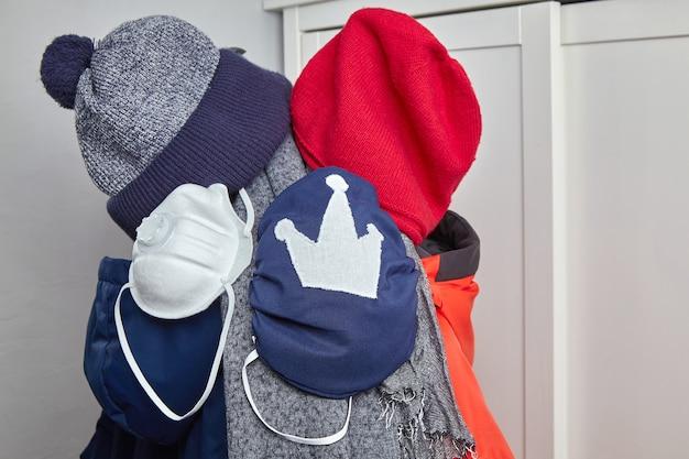 Защитные медицинские маски, висящие на вешалке с куртками и головными уборами. концепция сезонной защиты от вирусов. вторая волна коронавируса