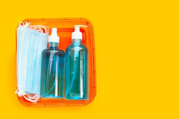 Защитные медицинские маски с дезинфицирующим средством жидкого геля на спирте и спреем на желтом фоне.