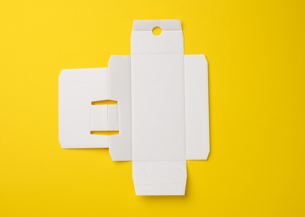 Protective paper from under a box with a perfume, template from white corrugated cardboard, yellow background