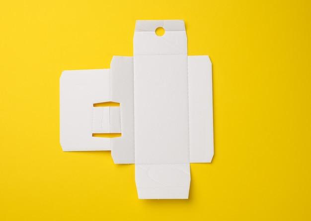 향수가 든 상자 아래의 보호지, 흰색 골판지 템플릿, 노란색 배경